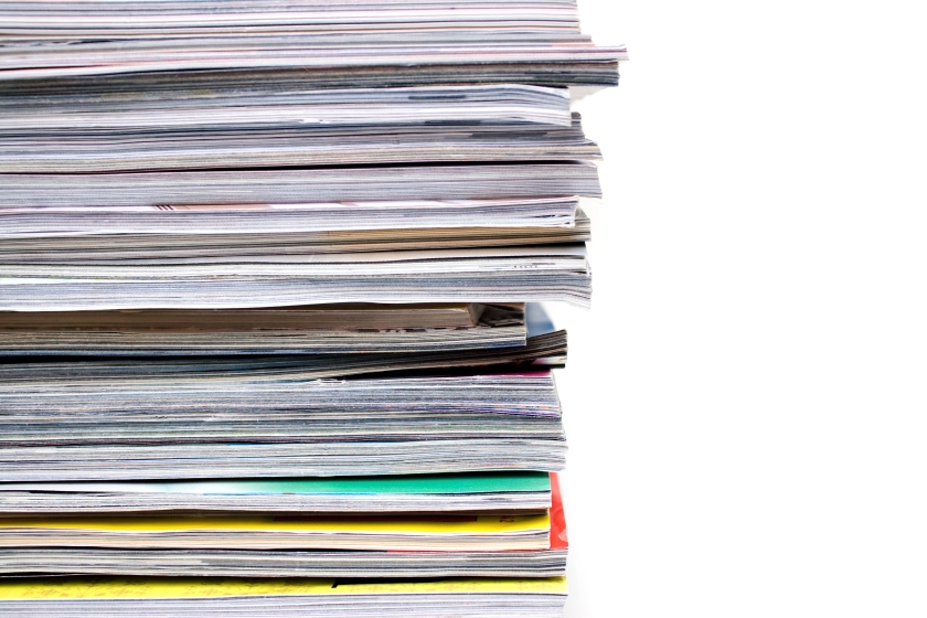 a-large-stack-of-magazines-piled-high-isolated-over-white-with-copyspace_rFzPOABi.jpg